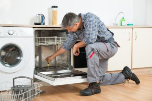 Repairman Fixing Dishwasher Covered Under A Home Warranty Plan