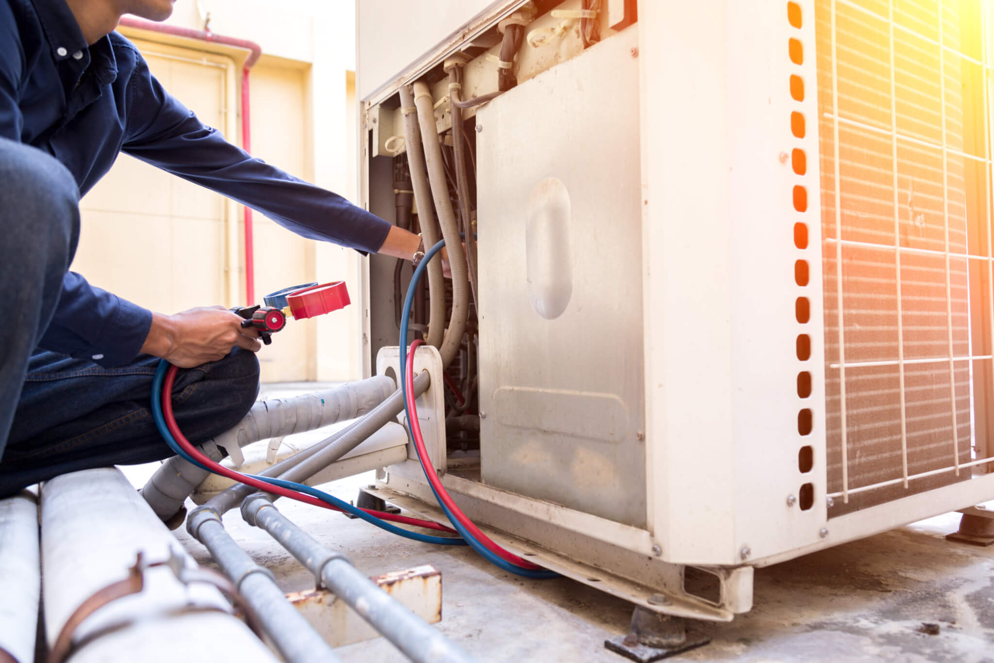 Technician is checking air conditioner during Rhode Island Summer covered by a home warranty