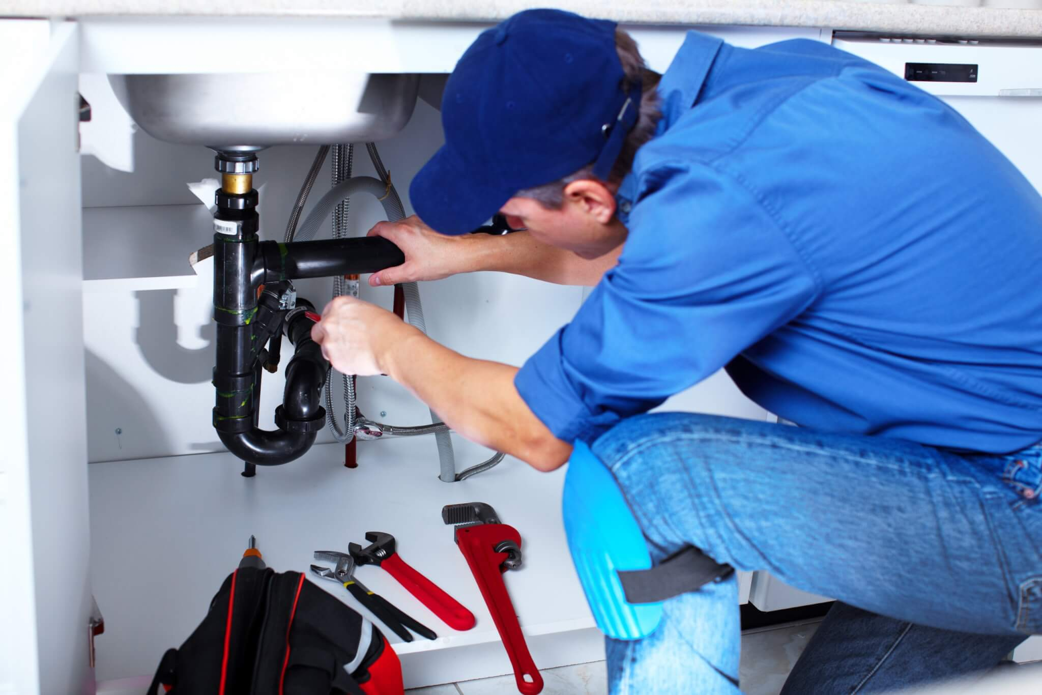 Professional plumber fixing a repair for a home warranty customer